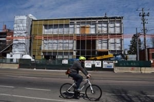 Brian Liberty cycling by new Humber College Athletic Building under construction on north side of Lake Shore Blvd. West, at a location west of Twenty Third St. in Long Branch. Just before taking this photo, Jaan Pill met Hayley Ryerson, a local musician who had just met with Brian Liberty regarding planning for future musical events in Long Branch. Jaan Pill photo