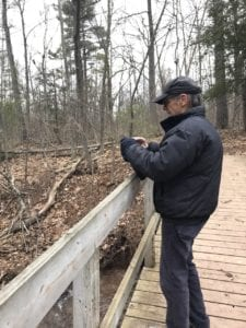 Picture-taker at footbridge, taking photo of stream at Terra Cotta Conservation Area (see photo below)